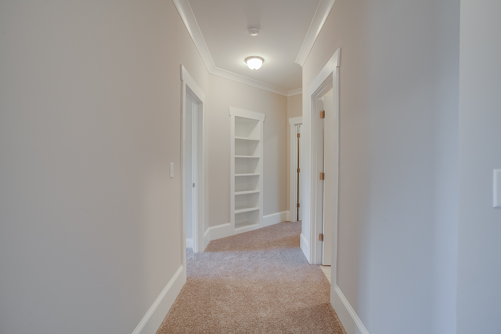 Hallway to back bedroom, laundry room on right, bedroom at the back and front bedroom door on left side